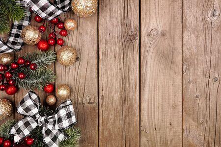 Weihnachtsseitenrand mit weiß-schwarz kariertem Büffel-Karoband, Dekorationen und Zweigen, oben auf einem rustikalen Holzhintergrund