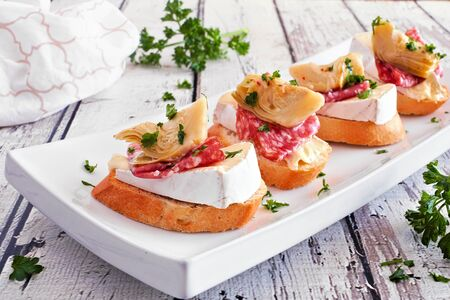 Crostini appetizers with brie cheese, salami and artichokes, close up on a plate against white wood