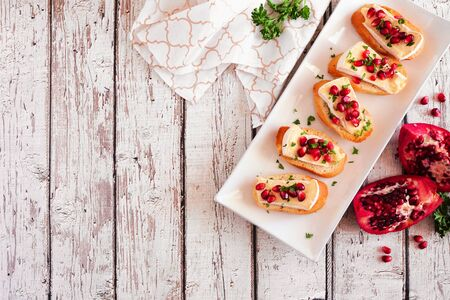 Holiday crostini appetizers with brie cheese, pomegranates and parsley, above view table scene against a white wood background with copy space