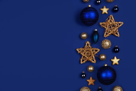 Christmas side border of dark blue and gold ornaments, top view on a blue background