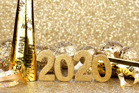 New Years Eve 2020 golden numbers and decorations with twinkling gold light background Stock Photo