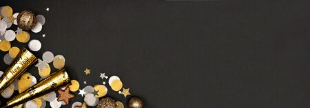 New Years Eve corner border banner of confetti, decorations and noisemakers, overhead view on a black background