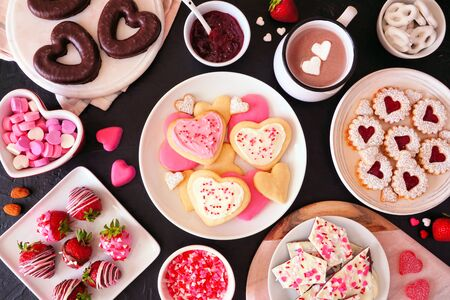 Valentines Day table scene with assorted sweets and cookies, above view over a dark Stock Photo - 137477154
