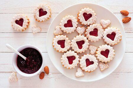 Biscotti alla marmellata di San Valentino con forme di cuore, scena del tavolo vista dall'alto contro il legno bianco