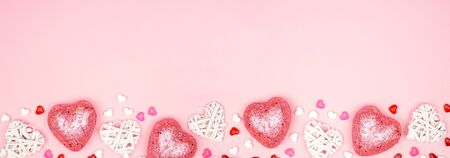 Valentines Day banner with long border of pink and white heart decorations against a pink
