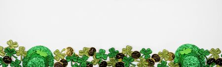 St Patricks Day banner border against a white background, above view with gold coins, shamrocks and leprechaun hats