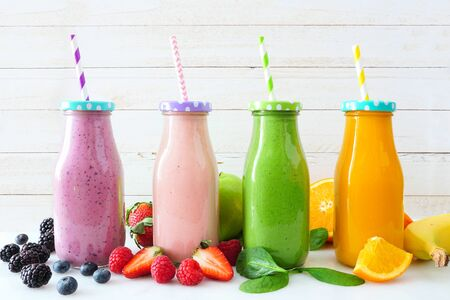 Various healthy smoothies in bottles with ingredients, side view against a white wood background