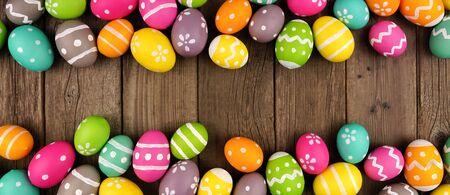 Striscione pasquale colorato con doppio bordo di uova di Pasqua su uno sfondo di legno scuro con spazio per le copie