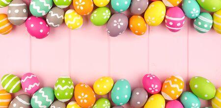 Striscione pasquale colorato con un doppio bordo di uova di Pasqua su uno sfondo di legno rosa con spazio per le copie
