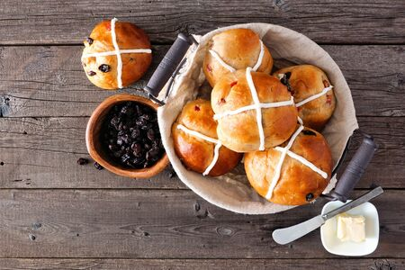 Basket of homemade Hot Cross Buns, top view over a wood background