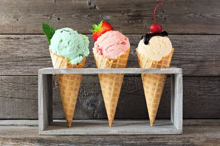 Ice cream cone assortment against a wood background, mint, strawberry and vanilla flavors Foto de archivo