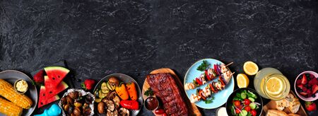 BBQ or summer picnic food border over a dark stone banner background, overhead view with copy space Foto de archivo