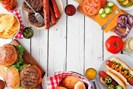 Summer BBQ food frame with hot dog and hamburger buffet, overhead against a white wood background 免版税图像
