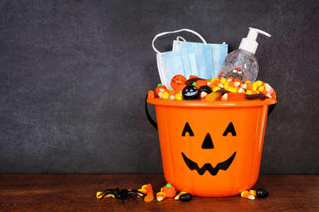 Halloween Jack o Lantern pail with candy and coronavirus prevention supplies on a shelf against a dark background