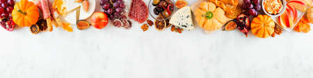 Fall charcuterie top border against a white marble banner background. Assorted cheese and meat appetizers. Copy space.