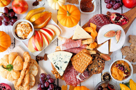 Fall theme charcuterie table scene against a white wood background. Assortment of cheese and meat appetizers. Above view.