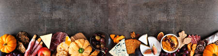 Fall charcuterie border against a dark stone banner background. Assorted cheese and meat appetizers. Copy space. Reklamní fotografie