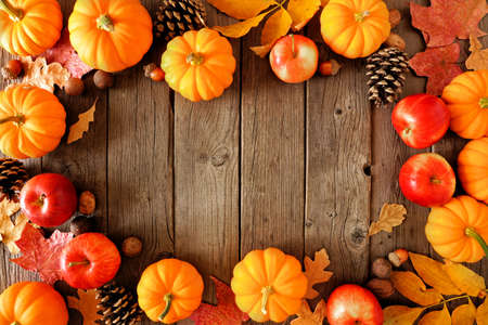 Autumn decor on a white shelf against a white wall background. Banner with copy space. Candle, branches, pumpkin.