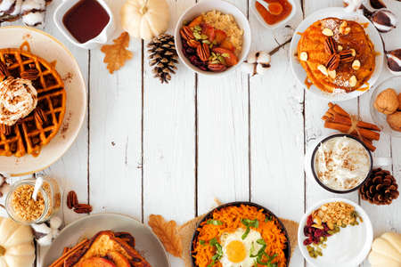 Autumn breakfast or brunch buffet frame against a white wood banner background. Pumpkin spice pancakes, waffles, apple french toast, oatmeal, egg skillet, yogurt. Overhead view with copy space. Stock Photo