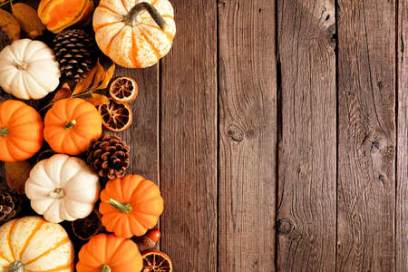 Autumn side border of pumpkins and natural fall decor. Overhead view on a rustic dark wood background with copy space.