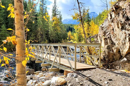 Bridge over rocky river bed in a mountain forest during autumn