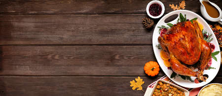 Traditional Thanksgiving turkey dinner. Overhead view side border on a dark wood banner background with copy space. Reklamní fotografie
