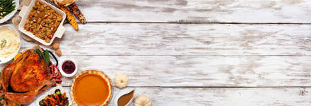 Traditional Thanksgiving turkey dinner. Top view corner border on a rustic white wood banner background with copy space. Turkey, mashed potatoes, stuffing, pumpkin pie and sides. Archivio Fotografico