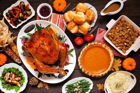 Classic Thanksgiving turkey dinner. Above view table scene on a dark wood background. Turkey, mashed potatoes, dressing, pumpkin pie and sides. Standard-Bild