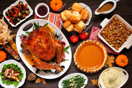 Classic Thanksgiving turkey dinner. Above view table scene on a dark wood background. Turkey, mashed potatoes, dressing, pumpkin pie and sides. Stock Photo