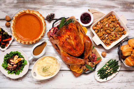 Classic Thanksgiving turkey dinner. Overhead view table scene on a rustic white wood background. Turkey, mashed potatoes, stuffing, pumpkin pie and sides. Reklamní fotografie