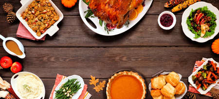 Classic Thanksgiving turkey dinner. Top view frame on a dark wood banner background with copy space. Turkey, mashed potatoes, dressing, pumpkin pie and sides. Reklamní fotografie