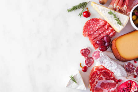 Selection of cheese and meat appetizers. Above view side border on a white marble background with copy space.