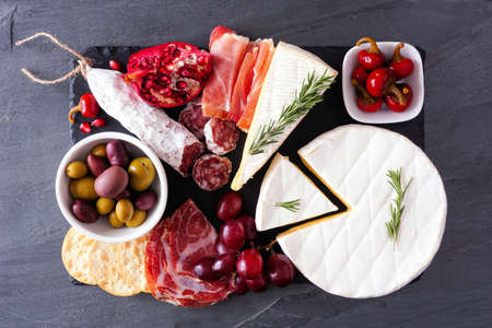 Charcuterie platter of assorted meats, cheeses and appetizers. Above view on a dark slate background.