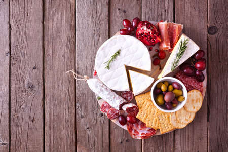 Platter of assorted meats, cheeses and appetizers. Overhead view on a rustic wood background.