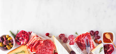 Variety of cheese and meat appetizers. Top view bottom border on a white marble banner background with copy space.