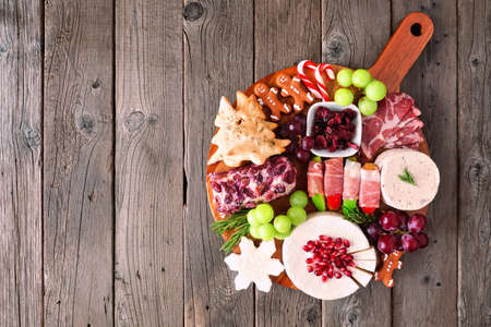 Christmas theme charcuterie board. Overhead view against a dark wood background. Mixed cheese and meat appetizers. Фото со стока