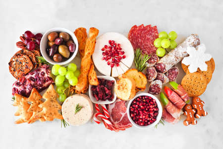 Christmas theme charcuterie board. Top view against a white wood background. Variety of cheese and meat appetizers.