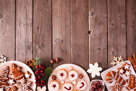 Christmas bottom border of assorted sweets and cookies. Top view over a rustic wood background. Holiday baking concept.