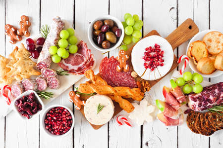 Christmas theme charcuterie table scene against a white wood background. Mixed cheese and meat appetizers. Top down view.