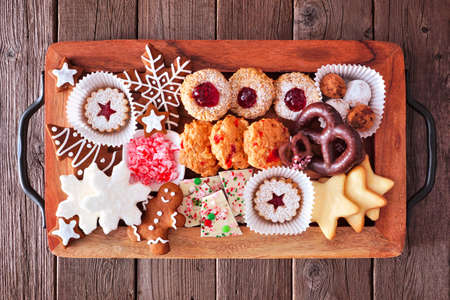 Tray of Christmas cookies and baked sweets. Top view over a rustic wood background. Holiday baking concept. 版權商用圖片