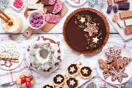 Assorted Christmas holiday desserts and sweets. Top view table scene over a white wood background. Bundt cake, chocolate pie, mincemeat tarts, cookies, fudge and eggnog. Imagens
