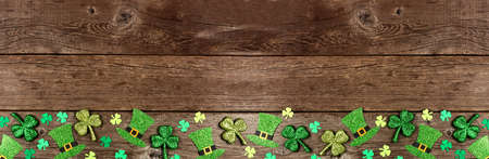 St Patricks Day shamrock and leprechaun hat bottom border. Top down view over a rustic wood banner background with copy space.