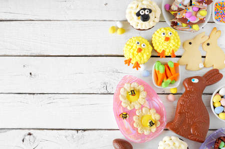 Easter table scene with an assortment of desserts and sweets. Above view side border over a white wood background. Spring holiday food concept. Copy space.