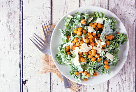 Vegetarian Caesar salad with chickpeas, kale and a yogurt dressing. Top view on a rustic white wood table background. Plant based food concept. Banque d'images