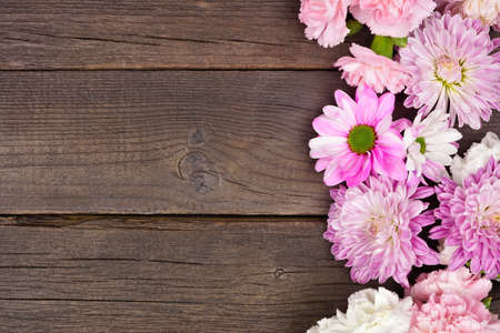 Side border of pink and purple flowers with mums, daisies and carnations against a dark wood background. Copy space.