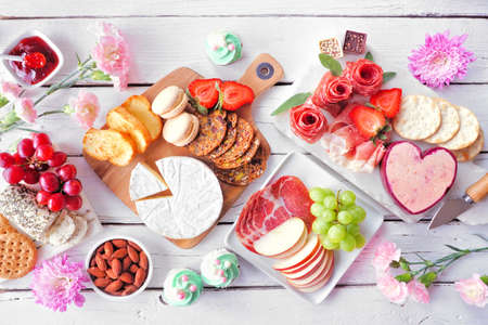 Mother's Day theme charcuterie table scene against a white wood background. Assortment of cheeses, meats, fruit and sweets. Above view.