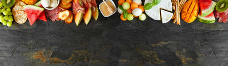 Summer fruit theme charcuterie corner border against a dark slate background. Assortment of fruits, cheese and meat appetizers. Copy space. Stock Photo