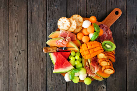 Summer fruit theme charcuterie board against a dark wood background. Selection of fruits, cheese and meat appetizers. Top view. Stock Photo