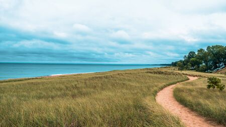 Dramatic landscape of lake michigan dunes and beach in New Buffalo Michigan. Sandy foot path leading to the beach before it rains.