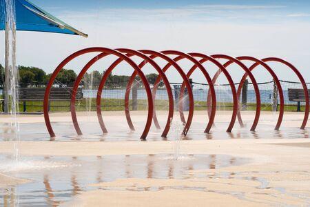 Red spraypad tunnel spraying water in the summer sun Banco de Imagens